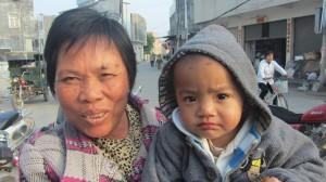 妇人带着孩子上街晒太阳。(中国妇权记者摄)xiao