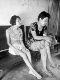 被拉到山西配阴婚的陕西残疾女陈某(左)已回到家中,因为智障,她尚不知道自己经历了一次生死劫难。