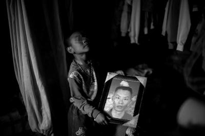 王光荣唯一的儿子手捧父亲遗像。网络截图