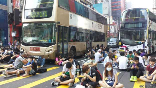 在旺角,示威者坐在马路中间,阻止巴士经过(BBC中文网记者萧尔摄)。