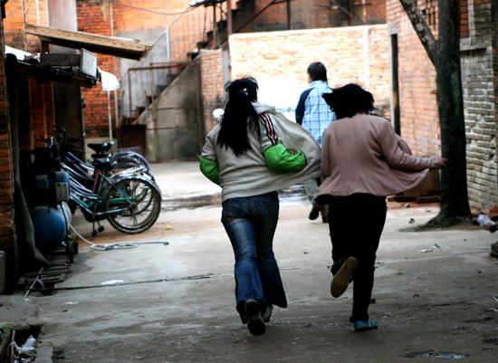 """2007年1月24日,福州查封无证工厂,十几名童工""""夺路而逃""""。视觉中国"""