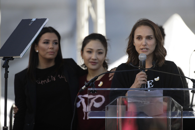 Actress Natalie Portman, right, speaks as she is joined by Eva Longoria, background left, and Constance Wu at a Women's March against sexual violence and the policies of the Trump administration Saturday, Jan. 20, 2018, in Los Angeles. (AP Photo/Jae C. Hong)