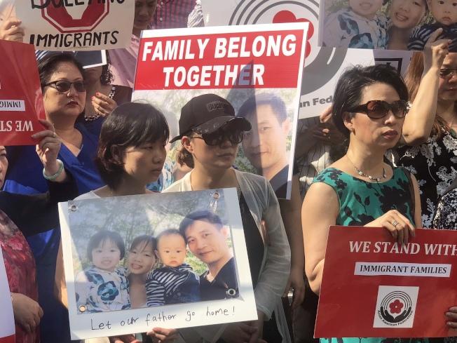 游秀清妻子陳玉梅(前排左一)手舉全家福照片在現場。(記者陳小寧/攝影)